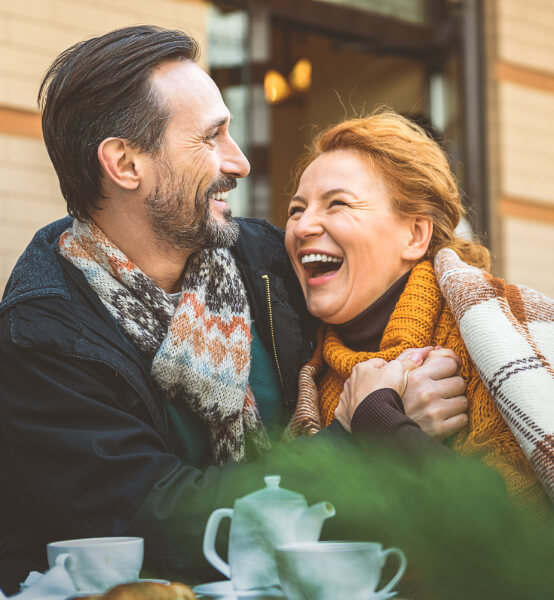 a man and a woman sitting outside laughing