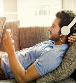 a guy laying on his couch, checking his phone, wearing headphones